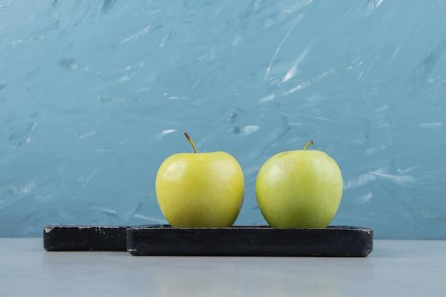 Duas maçãs verdes frescas na tábua de corte preta