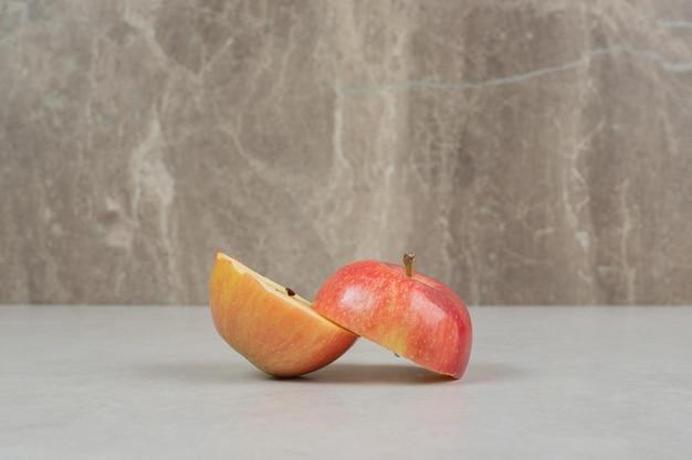 Duas maçãs vermelhas cortadas pela metade na mesa cinza
