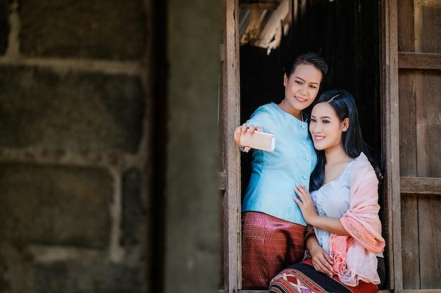 Duas mãe e filha em um vestido tradicional tailandesa estão tirando fotos de si mesmos com um telefone móvel de uma janela de madeira.