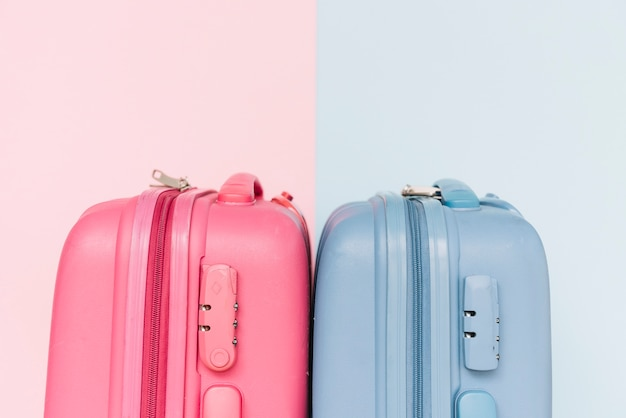Duas malas de bagagem de plástico azul e rosa em fundo duplo