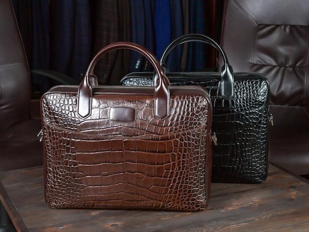 Duas malas de viagem feitas de couro de crocodilo no fundo da coleção de roupas masculinas