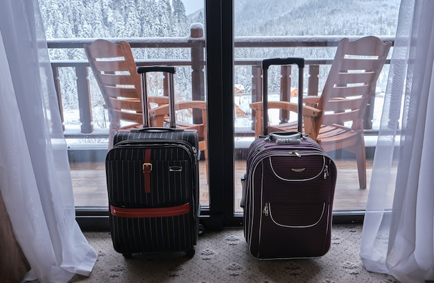 Duas malas estão em frente à janela panorâmica do apartamento do hotel, com uma vista deslumbrante das montanhas cobertas de neve