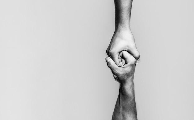 Duas mãos, ajudando o braço de um amigo, trabalho em equipe. conceito de mão amiga e dia internacional da paz, apoio. preto e branco.