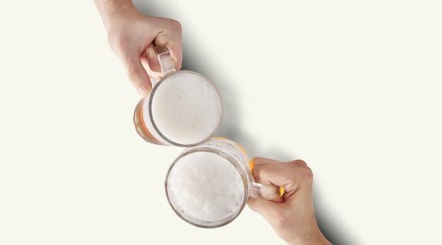 Duas mãos brindando uma cerveja gelada refrescante.