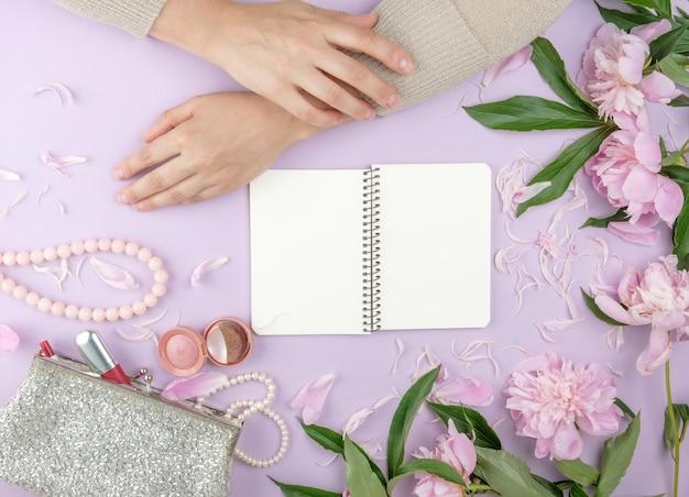 Duas mãos com a pele lisa de uma jovem e uma bolsa com cosméticos, buquê de peônias rosa florescendo, conceito moderno, vista superior