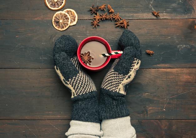 Duas mãos com luvas de malha marrons segurando um copo vermelho com uma bebida em uma mesa de madeira marrom