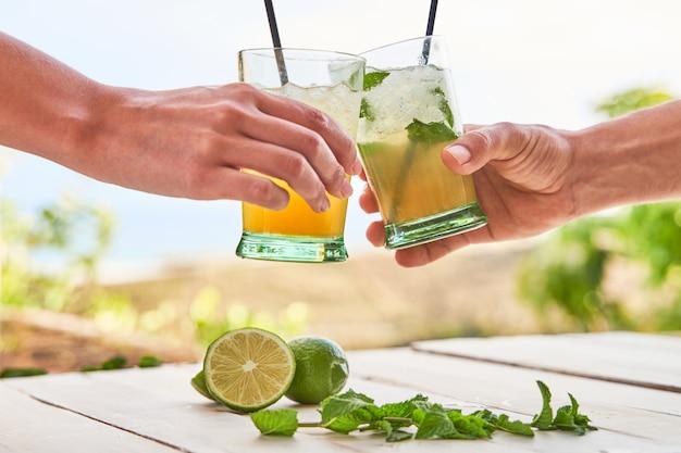 Duas mãos com mojitos brindando, com a praia ao fundo. conceito de bebida para o verão.