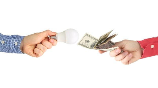 Duas mãos com notas de dólar e lâmpada led em um branco