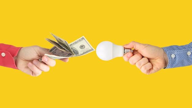 Duas mãos com notas de dólar e lâmpada led em uma laranja brilhante. pagamento de eletricidade. compre lâmpada led. indústria de negócios