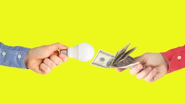 Duas mãos com notas de dólar e lâmpada led em uma laranja brilhante.