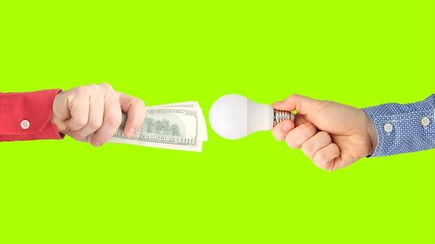 Duas mãos com notas de dólar e lâmpada led. pagamento de eletricidade. compre lâmpada led. indústria de negócios