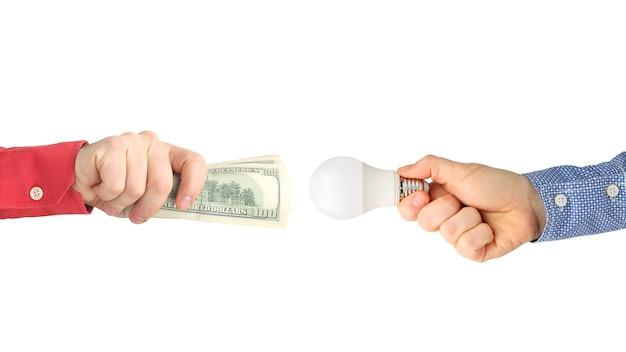 Duas mãos com notas de dólar e uma lâmpada led em branco.