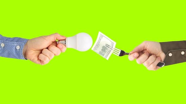 Duas mãos com notas de dólar e uma lâmpada led em um fundo verde brilhante.