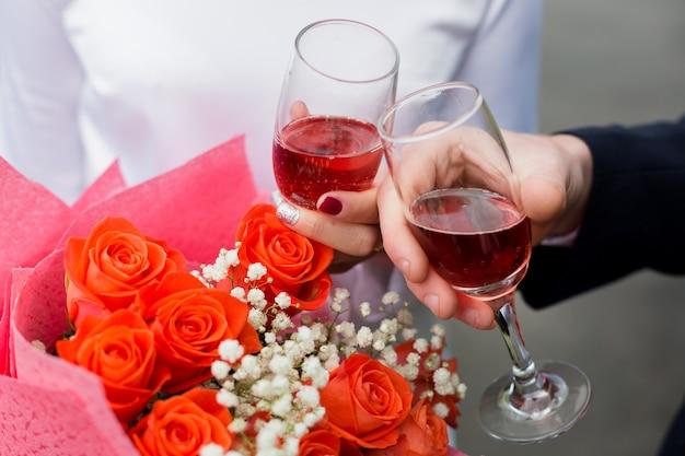 Duas mãos com óculos em um fundo de flores.