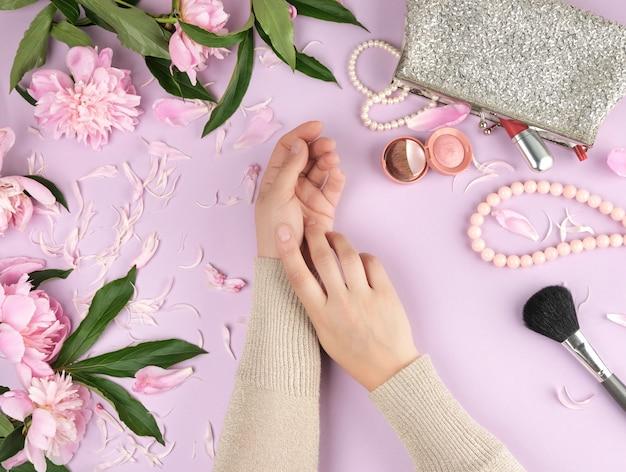 Duas mãos, com, pele lisa, de, um, menina jovem, e, um, bolsa, com, cosméticos