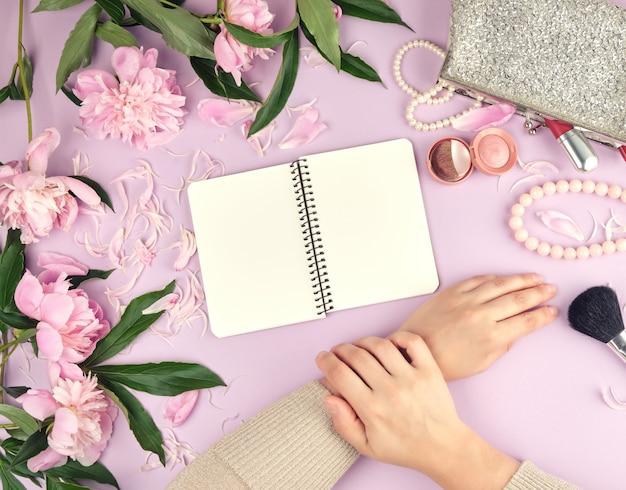 Duas mãos com pele lisa de uma jovem e uma bolsa com cosméticos, buquê de peônias rosa desabrocham