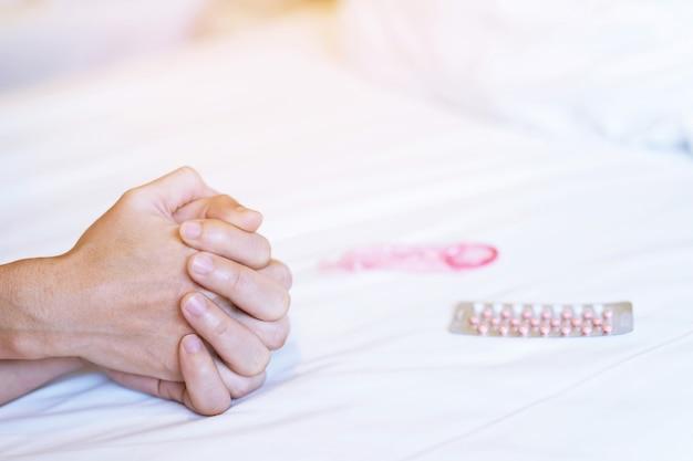 Duas mãos de amantes na cama durante a atividade, preservativo borrado e embalagem de pílulas anticoncepcionais