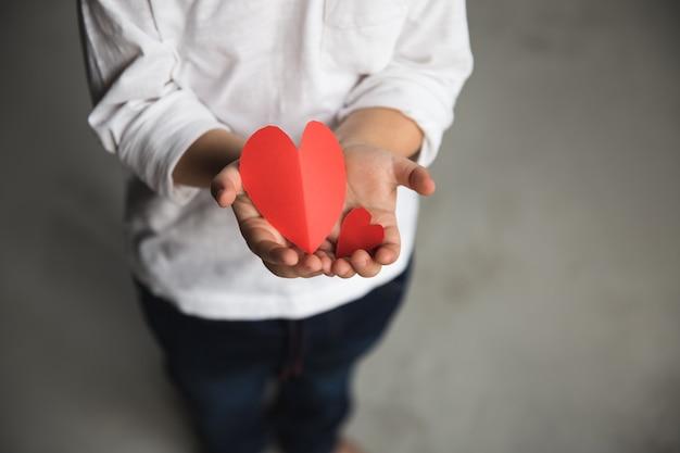 Duas mãos de bebê segurando corações de papel vermelho.
