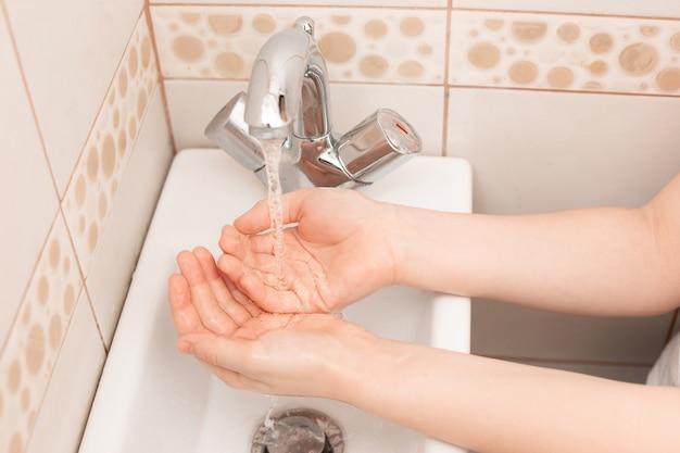 Duas mãos de criança acima da pia no banheiro com água vertendo