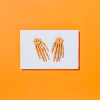 Duas mãos de esqueleto colocadas em pedaço de papel branco