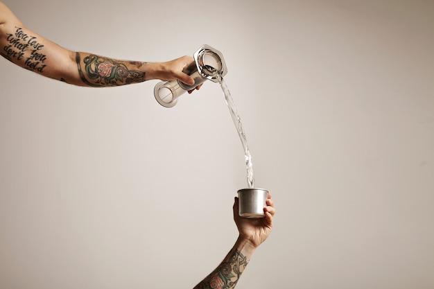 Duas mãos de homem tatuado derramando água de um aeropressor de plástico transparente em um pequeno copo de aço para viagem.