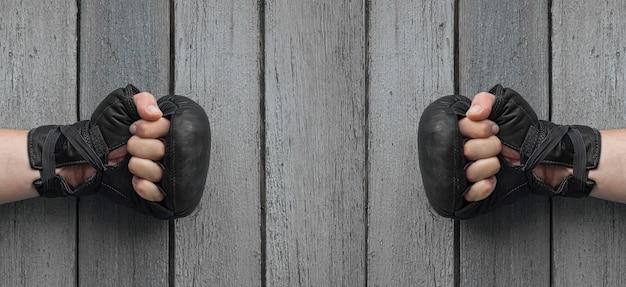 Duas mãos de homens em luvas de couro preto para boxe tailandês