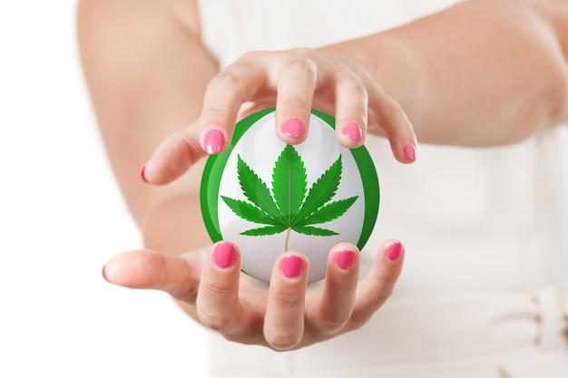 Duas mãos de mulher protegendo a esfera com o ícone de folha de cânhamo ou maconha medicinal em um fundo branco.
