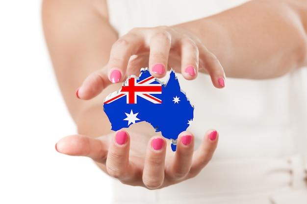 Duas mãos de mulher protegendo o mapa da austrália com a bandeira em um fundo branco.
