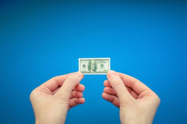 Duas mãos de mulher segurando pequenas notas de 100 dólar dos eua