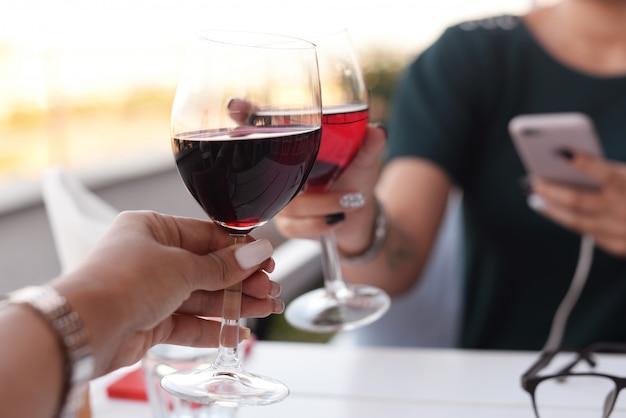 Duas mãos de uma menina em um lindo restaurante em uma mesa segurando óculos
