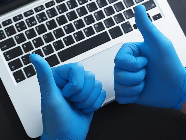 Duas mãos em luvas azuis, mostrando os polegares, laptop portátil.