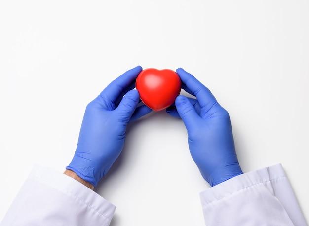 Duas mãos em luvas de látex azuis segurando um coração vermelho, conceito de doação, close-up