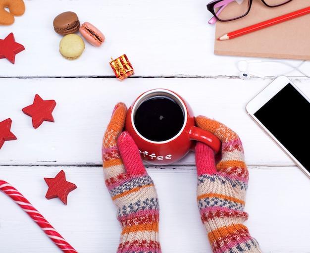 Duas mãos em luvas de malha segurar um copo vermelho com café