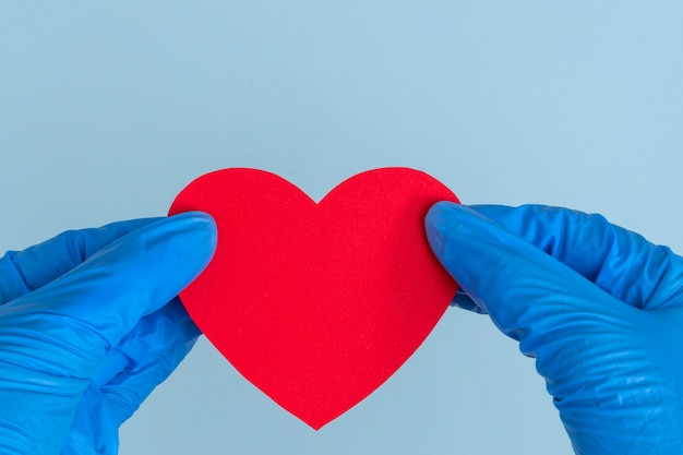 Duas mãos em luvas médicas azuis segurando um modelo em forma de coração vermelho sobre fundo azul