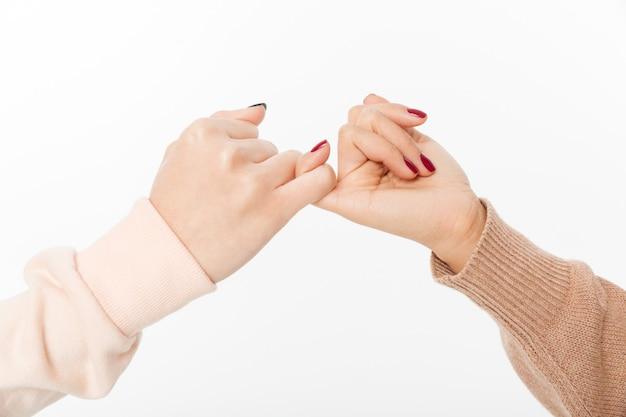 Duas mãos engancham o dedo mindinho um do outro