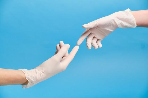 Duas mãos enluvadas se tocam durante a quarentena de coronavírus pandêmica. conceito de sexo protegido. conceito de quarentena.