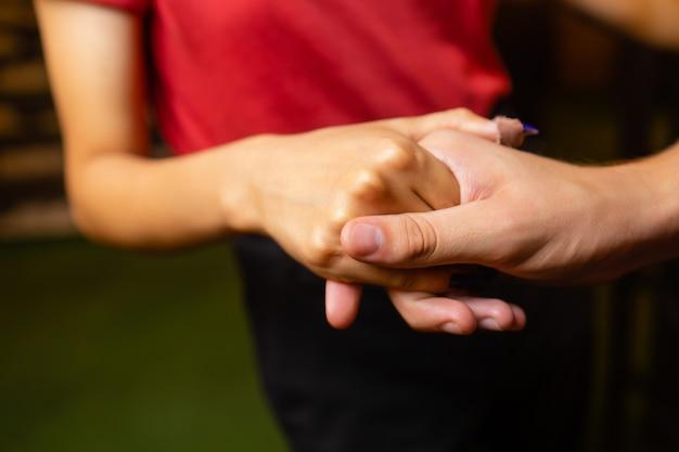 Duas mãos fechadas juntas ao ar livre e o casal ama no fundo da natureza