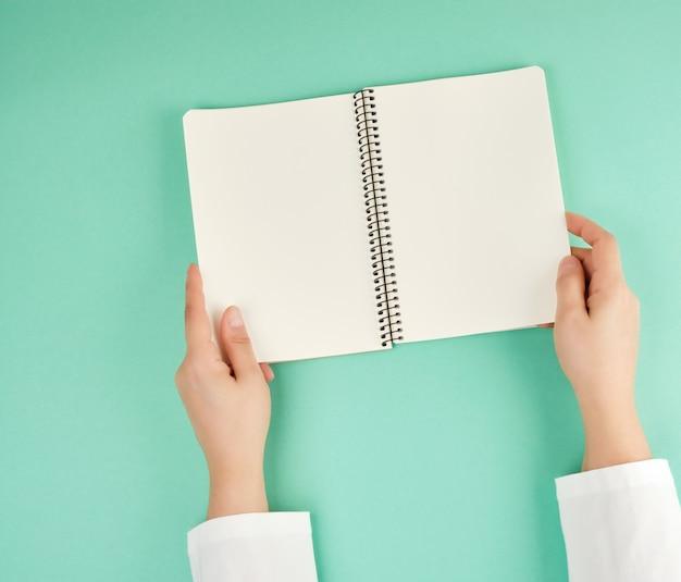 Duas mãos fêmeas que prendem o bloco de notas em branco aberto com folhas limpas. copyspace