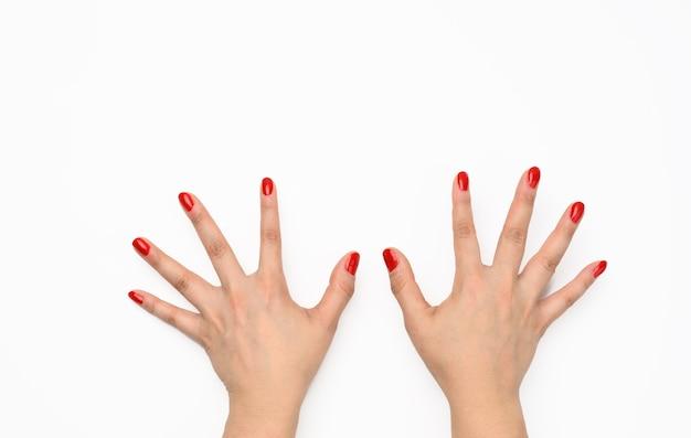 Duas mãos femininas com manicure vermelha levantadas sobre um fundo branco