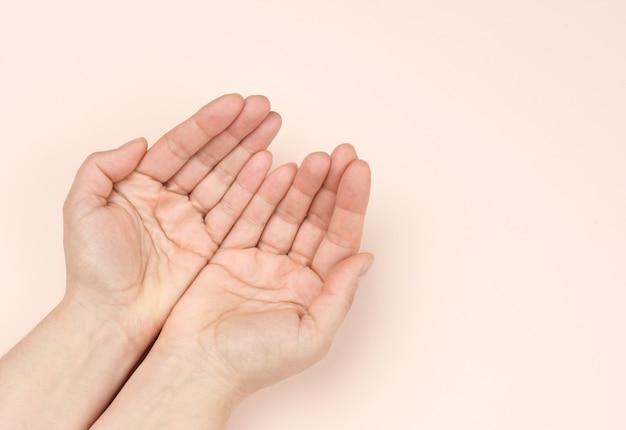 Duas mãos femininas cruzadas palma com palma em um fundo bege, vista superior