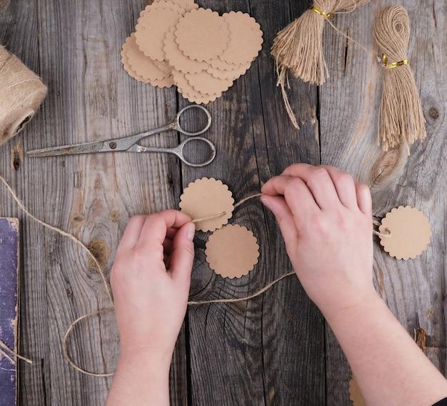 Duas mãos femininas e etiquetas de papel com uma corda marrom em uma mesa de madeira cinza