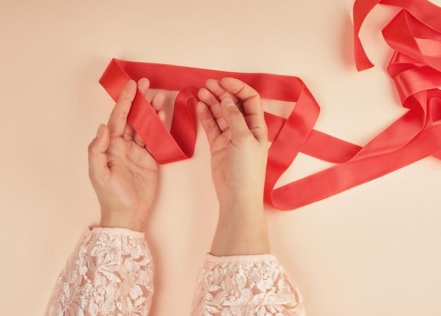 Duas mãos femininas e fita de seda vermelha