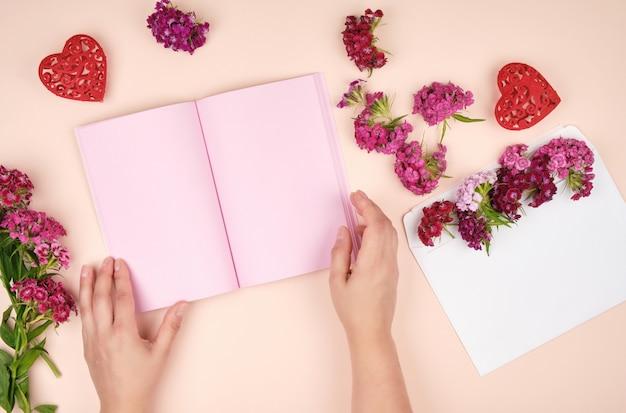 Duas mãos femininas e um caderno aberto com folhas em branco-de-rosa