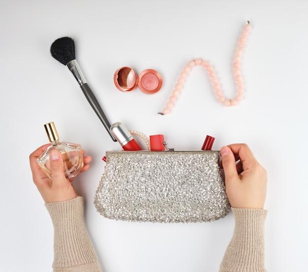 Duas mãos femininas e um saco de cosmética prata com cosméticos
