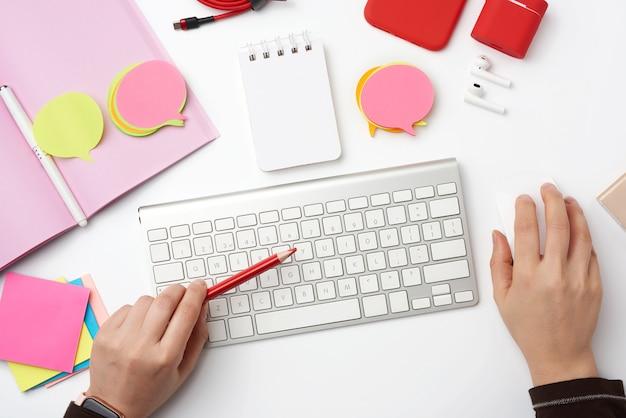 Duas mãos femininas e um teclado branco, local de trabalho freelancer com um caderno aberto