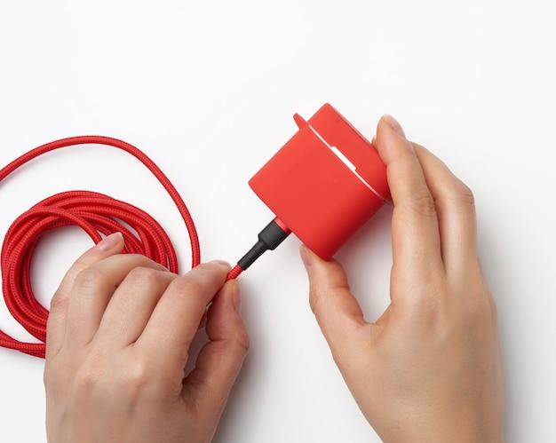 Duas mãos femininas estão segurando um cabo e uma caixa vermelha com fones de ouvido sem fio