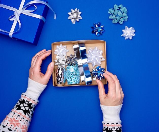 Duas mãos femininas estão segurando uma caixa de papelão marrom com um conjunto de fitas e laços de decoração para embrulhar presentes