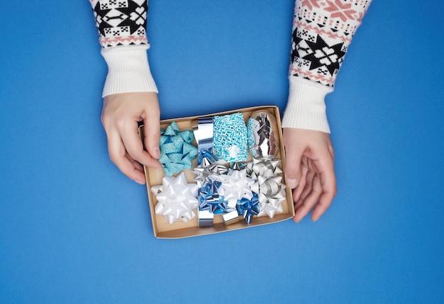 Duas mãos femininas estão segurando uma caixa de papelão marrom com um conjunto de fitas e laços de decoração