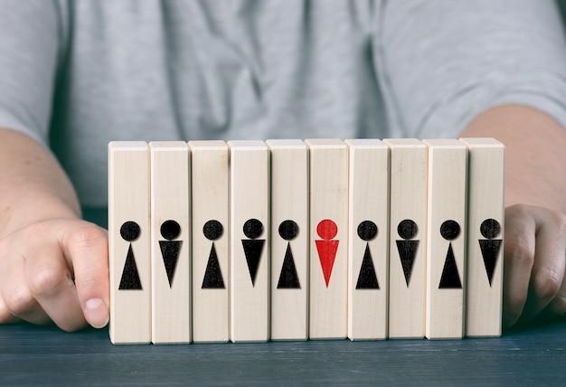 Duas mãos femininas seguram cubos de madeira com homenzinhos em uma mesa azul. conceito de cuidado da equipe, escolha do líder, coesão da equipe, recrutamento de pessoal