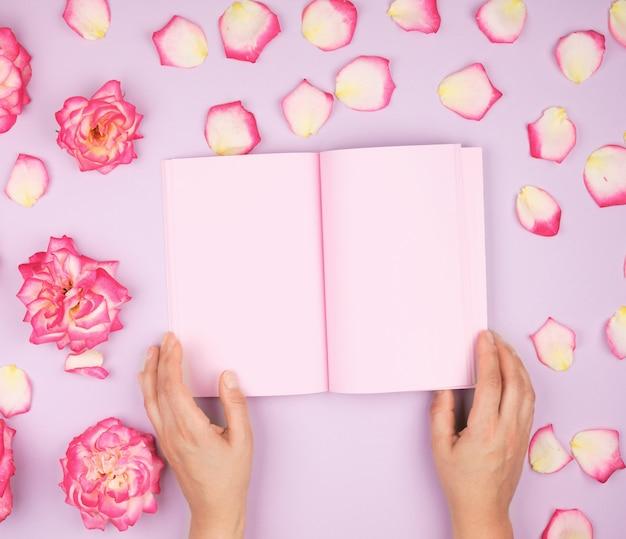 Duas mãos femininas segurando o bloco de notas aberto com lençóis cor de rosa limpos